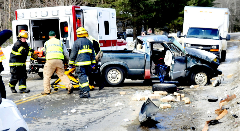 SERIOUS: Madison firefighters and ambulance personnel load one of two injured occupants of a pick-up truck that was hit by a delivery truck on Old County Road in Madison on Wednesday. Jon Bachelder, the driver of the delivery truck, said his shoelaces got tangled in his gas pedal and the truck went through a stop sign at the intersection, police said.