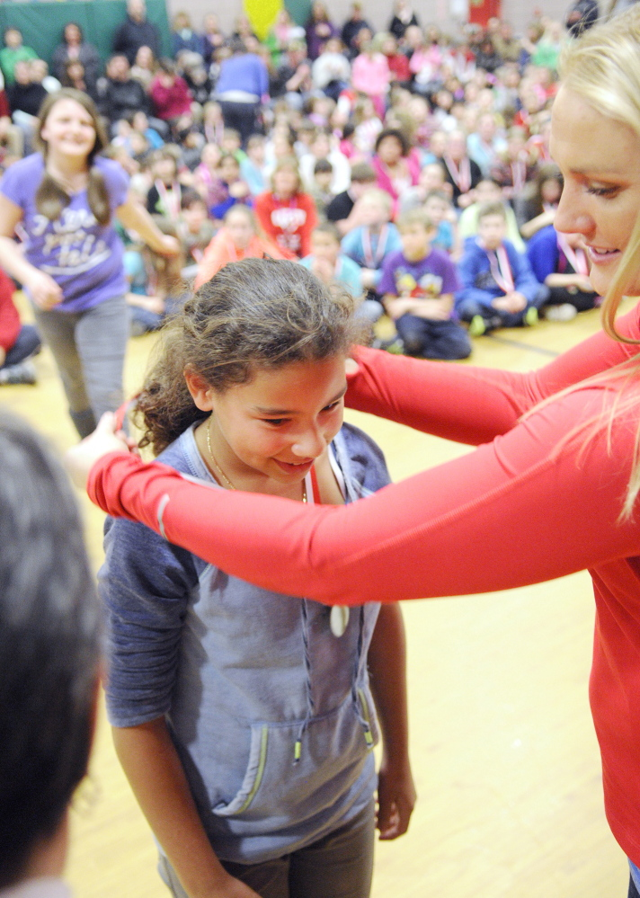 ACHIEVEMENT: Jasmine Daley, left, gets a medal from Olympic luger Julia Clukey during a medal ceremony for academic test scores on Thursday at Farrington School in Augusta.