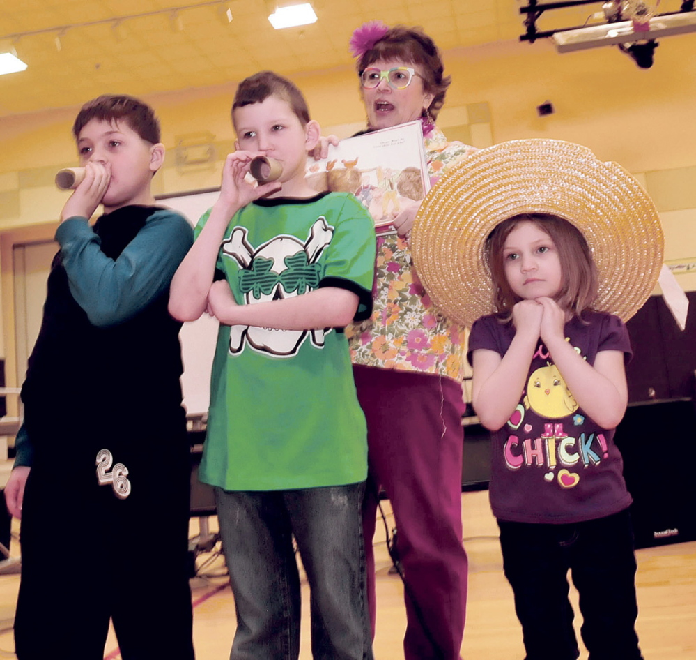 "IN CHARACTER: Author Lynn Plourde directs Madison Elementary School students who were dressed as characters from her new book titled ""You're Wearing THAT To School?"" on Thursday at the school. From left are Griffin Aldrich, Matt Hurst, Plourde and Alyssa Burrows."