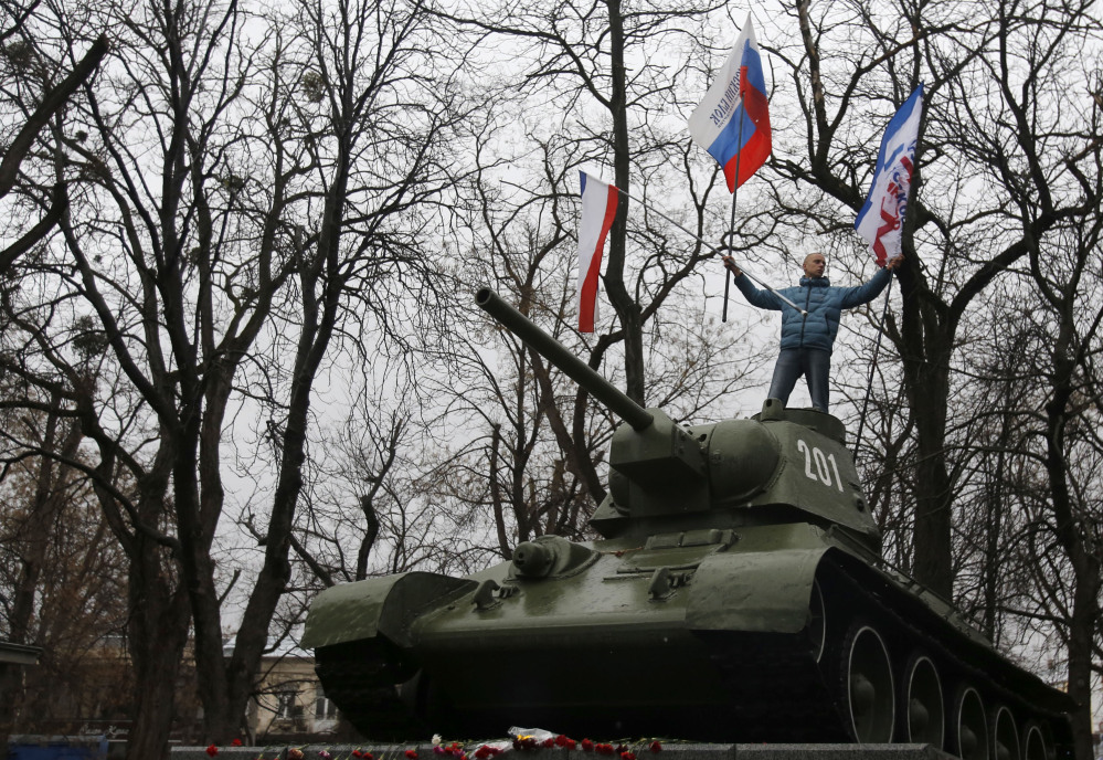 A Pro-Russian demonstrator waves Russian and Crimea flags from an old Soviet Army tank during a protest in front of a local government building in Simferopol, Crimea, Ukraine, on Thursday. Ukraine's acting interior minister said dozens of men seized local government and legislature buildings in the Crimea region.