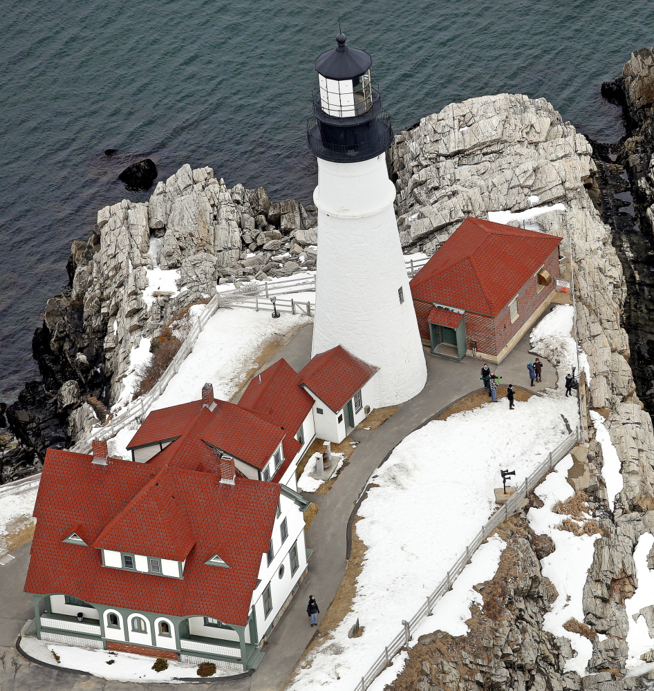 Tourists visit Portland Head Light in Cape Elizabeth on Tuesday. The town is looking at a project that would enhance the surrounding landscape.