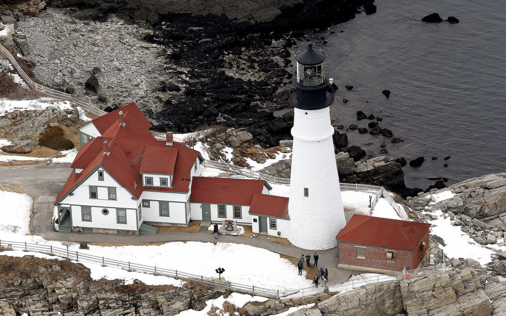 Tourists visit Portland Head Light in Cape Elizabeth on Tuesday. Stone seating is part of an improvement plan at the park.