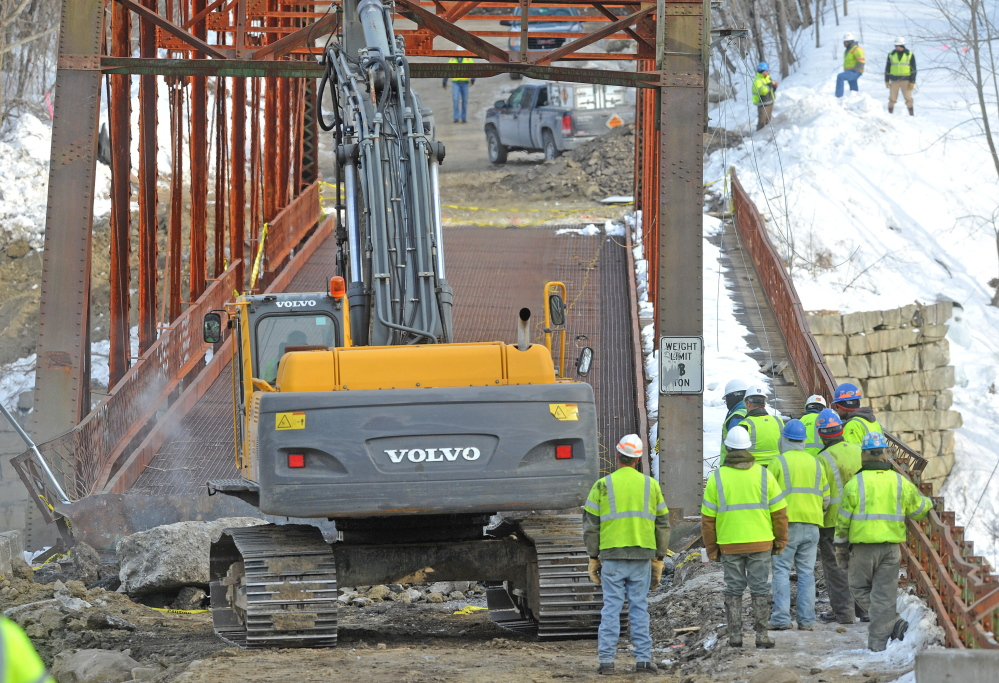 BRIDGE WORK: Crews stand by as an excavator jackhammers the New Sharon bridge on Thursday. The initial controlled explosions failed to bring down the historic bridge, but it was brought down several hours later by excavators.