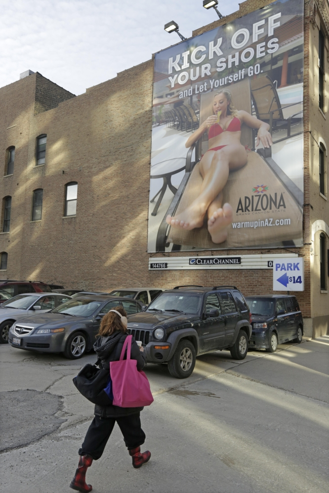 In this Wednesday, Feb. 26, 2014 photo, a pedestrian in Chicago walks bundled up for the cold weather past an advertisement touting the warmth of Arizona. With yet another polar vortex like storm system bearing down on many parts of the country, suffering Midwesterners dream about being anywhere but home. Tourist operations have been fueling this with email and other ad campaigns dangling a little sunshine and beach scenes in front of us.