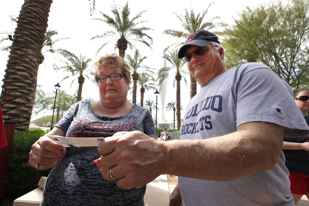 In this photo taken Wednesday, Feb. 26, 2014, Sue Knieriemen, of Fremont, Ohio, and her brother Charles Bork, of Sylvania, Ohio, check their tickets outside Goodyear Ballpark before an exhibition baseball game between the Cincinnati Reds and the Cleveland Indians in Goodyear, Ariz. After such a long, cold season, Americans across the winter-weary Midwest and the East Coast are desperate to escape to warm-weather destinations in California, Arizona and Florida.