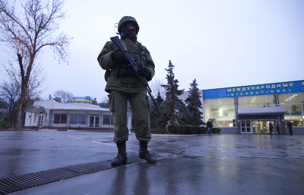 An unidentified man patrols a square in front of the airport in Simferopol, Ukraine, on Friday. Dozens of armed men in military uniforms without markings occupied the airport in the capital of the strategic Crimea region.