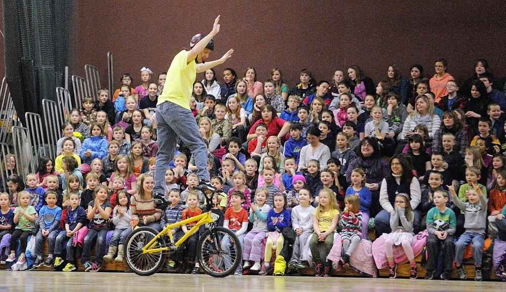 LIFE TRICKS: World Champion Bicycle Stunt Rider, Motivational Speaker and Author Chris Poulos does a trick as he talks to Cottrell School students in the Foster Memorial Gym at Monmouth Academy about bullying and other topics on Friday.