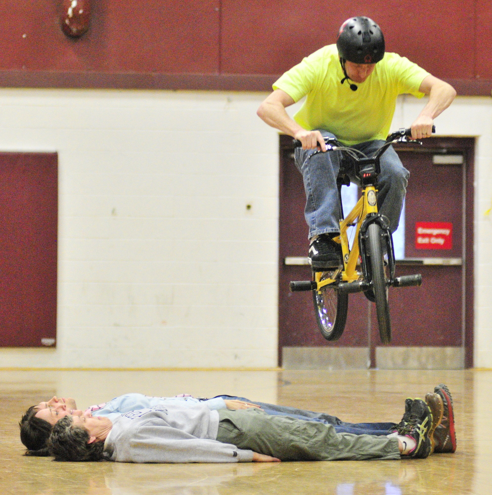 LIFE TRICKS: Chris Poulos, World Champion Bicycle Stunt Rider, Motivational Speaker and Author, jumps over three faculty members as the finale to his afternoon of bike tricks and a talk to Cottrell School students in the Foster Memorial Gym at Monmouth Academy on Friday.