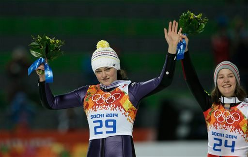 Germany's Carina Vogt celebrates winning the gold as France's bronze medal winner Coline Mattel looks on during the women's normal hill ski jumping final at the 2014 Winter Olympics, Tuesday, Feb. 11, 2014, in Krasnaya Polyana, Russia.