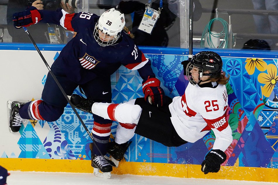 Kendall Coyne of the Untied States collides with Alina Muller of Switzerland against the boards during the first period of the 2014 Winter Olympics women's ice hockey game at Shayba Arena, Monday, Feb. 10, 2014, in Sochi, Russia. (AP Photo/Petr David Josek) 2014 Sochi Olympic Games;Winter Olympic games;Olympic games;Spor