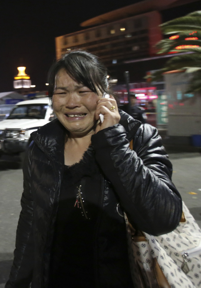 A woman makes a call from the crime scene outside a railway station in Kunming, China, on Saturday.