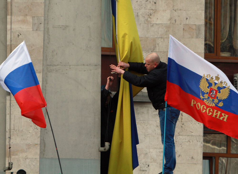 Pro-Russian activists remove the Ukrainian flag, center, to replace it with a Russian one on an administration office in the center of Donetsk, Ukraine, on Saturday. Supporters of new Ukrainian authorities and pro-Russia demonstrators clashed in Kharkiv and Donetsk a mostly Russian-speaking region in eastern Ukraine.