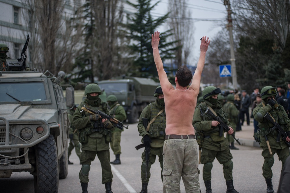 A Ukrainian man stands in protest in front of gunmen in unmarked uniforms as they stand guard in Balaklava, on the outskirts of Sevastopol, Ukraine, on Saturday. An emblem on one of the vehicles and their number plates identify them as belonging to the Russian military.