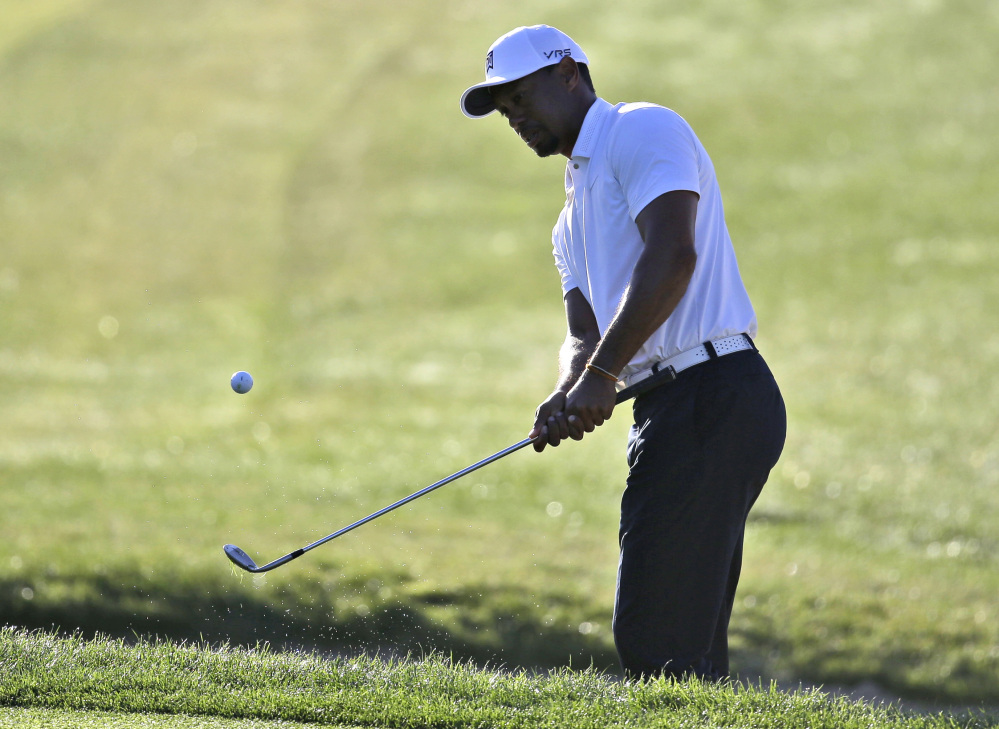 Tiger Woods hits from a bunker onto the second hole during the third round of the Honda Classic golf tournament on Saturday in Palm Beach Gardens, Fla. Woods shot a 65.