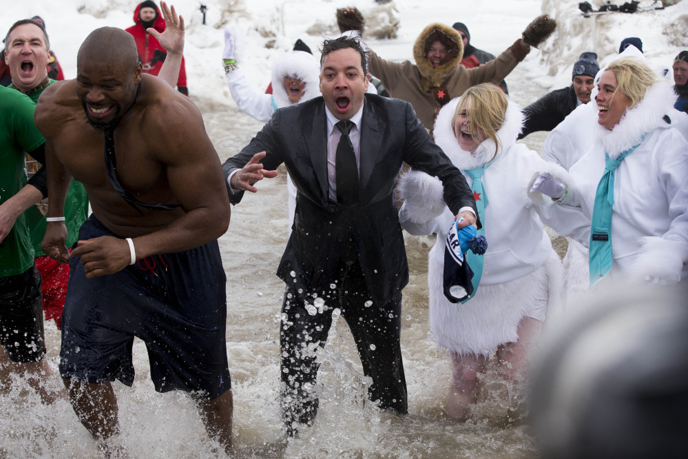 """The Tonight Show"" host Jimmy Fallon, center, exits the water during the Chicago Polar Plunge on Sunday in Chicago. Fallon joined Chicago Mayor Rahm Emanuel in the event."