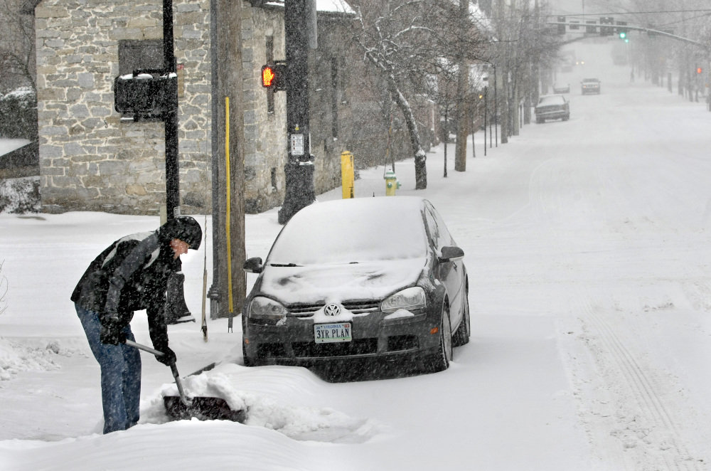 Tom Stark shovels snow from the sidewalk and driveway on Monday in Winchester, Va.
