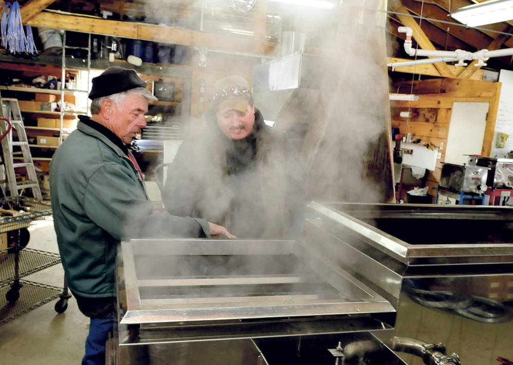 BOILING READY: Bob Bacon, left, of the Bacon Farm in Sidney, speaks with Jim Wright of Apple Ridge maple syrup operation in Cornville as steam rises from a sap evaporator in Sidney on Monday, March 3, 2014. Bacon said it was the second time he boiled syrup this season and expects his operation to increase this weekend as temperatures rise.