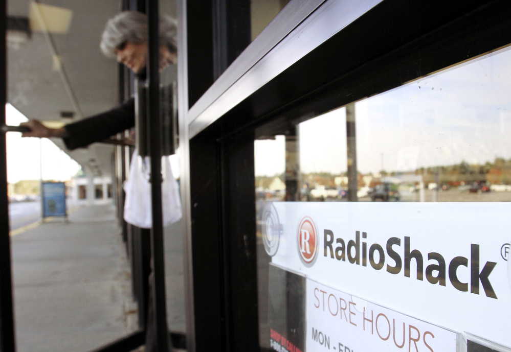 A shopper leaves a RadioShack store in Brunswick. The electronics retailer on Tuesday said it plans to close up to 1,100 of its underperforming stores in the U.S.