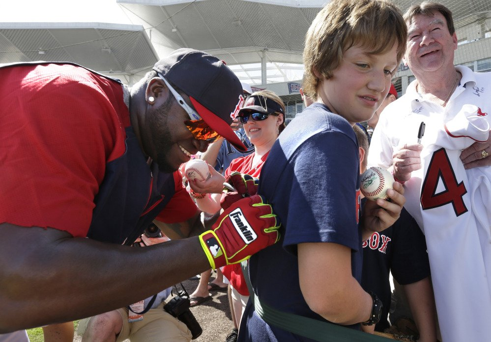 HAPPY FANS: Boston Red Sox designated hitter David Ortiz, left, signs an autograph on a shirt for Kobe Kellar of Orange Park, Fla. on Tuesday before an exhibition game against the Tampa Bay Rays. The Rays won 8-0 over the Red Sox.