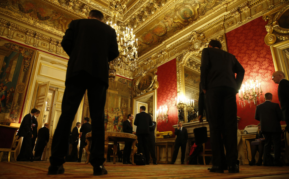 Delegation members wait outside the meeting room where foreign ministers, including Russian Foreign Minister Sergei Lavrov and Secretary of State John Kerry, were discussing the Ukraine crisis, Wednesday, March 5, 2014, at the Quai d'Orsay in Paris.
