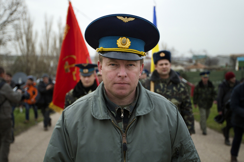 Col. Yuri Mamchur, commander of the Ukrainian garrison at the Belbek airbase, leads his men to the base outside Sevastopol, Ukraine, Tuesday. Russian troops, who had taken control over Belbek airbase, fired warning shots in the air as around 300 Ukrainian officers marched toward them to demand their jobs back.