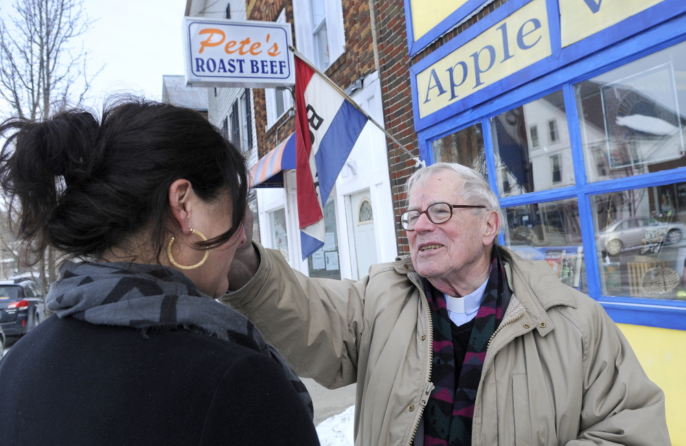 ASHES TO GO: The Rev. James Gill, of St. Andrew's Episcopal Church, smudges ashes Wednesday on Kim Cognata's forehead on the first day of Lent in downtown Winthrop. Gill took the ashes, a Christian symbol of repentance before God, to the streets as an extension of services at his Winthrop church. Cognata co-owns The Flaky Tart Cafe in Winthrop.