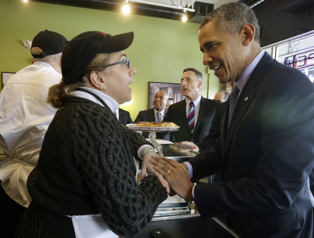 President Obama greets Café Beauregard owner Alice Bruno during his unannounced visit to the café in New Britain, Conn., on Wednesday. Also at the counter with Obama are Massachusetts Gov. Deval Patrick, center, and Vermont Gov. Peter Shumlin.
