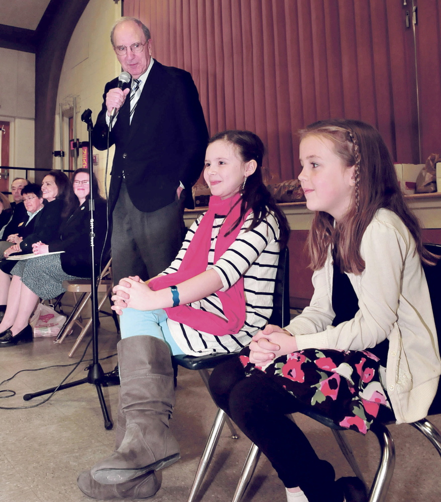 YOUNG STARS: Former U.S. Sen. George Mitchell pays tribute to students Gabbie St. Peter, left, and Alice Willette during an assembly Wednesday at George J. Mitchell School in Waterville. The second-graders were honored for their efforts to raise money and awareness for the school food pantry when they asked for donations rather than birthday presents.