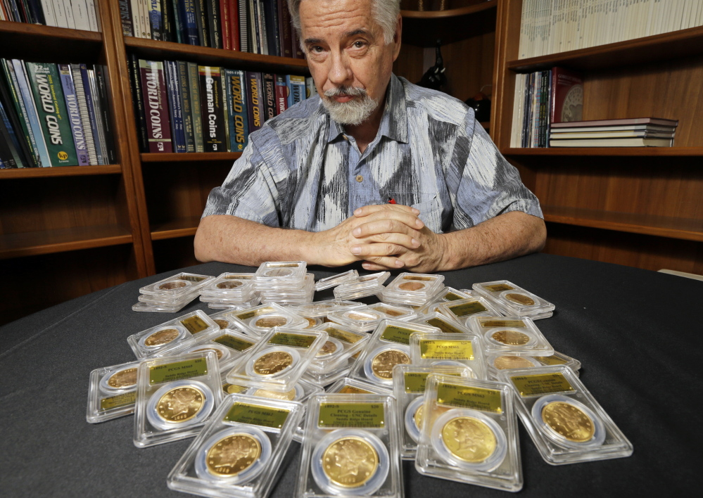 David Hall, co-founder of Professional Coin Grading Service, poses with some of 1,427 Gold Rush-era U.S. gold coins, at his office in Santa Ana, Calif. A California couple out walking their dog on their property stumbled across the bonanza.