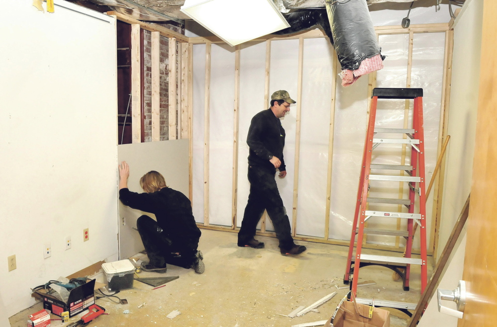 WORK IN PROGRESS: Waterville Public Works employees Jacob Chambers, left, and Dan Main renovate a former city detective's office in the City Hall basement on Thursday. The former police station space will be used for storage.
