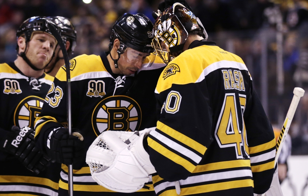 Boston Bruins goalie Tuukka Rask (40) bumps foreheads with teammate Chris Kelly after the Bruins defeated the Washington Capitals 3-0 during an NHL hockey game, Thursday, March 6, 2014, in Boston. At left is Bruins right wing Shawn Thornton.