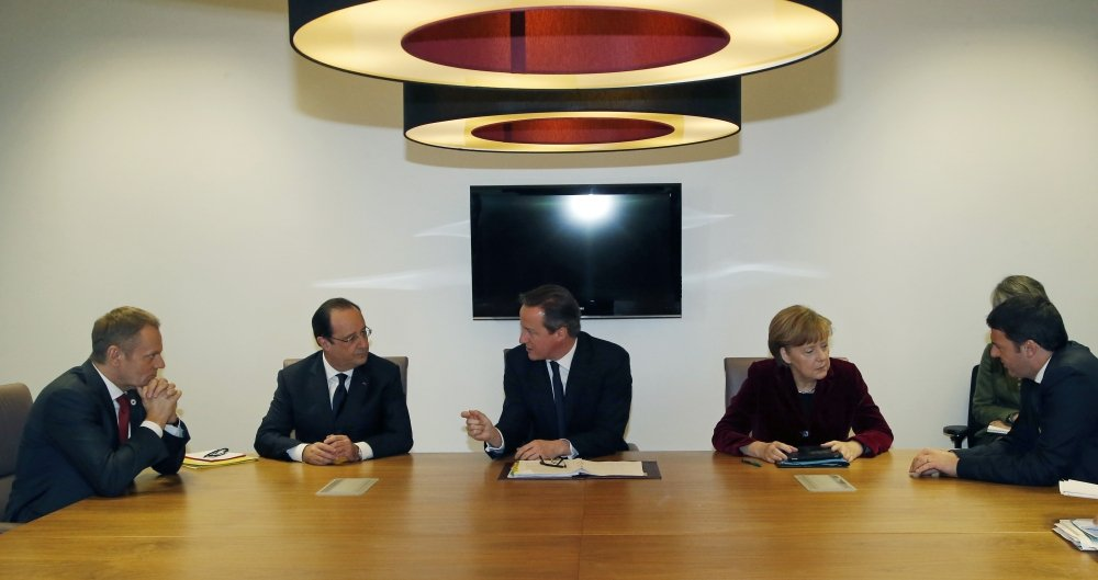 From left, Polish Prime Minister Donald Tusk, French President Francois Hollande, British Prime Minister David Cameron, German Chancellor Angela Merkel and Italian Prime Minister Matteo Renzi speak with each other during a meeting at an EU summit in Brussels on Thursday, March 6, 2014. EU heads of state meet Thursday in emergency session to discuss the situation in Ukraine.