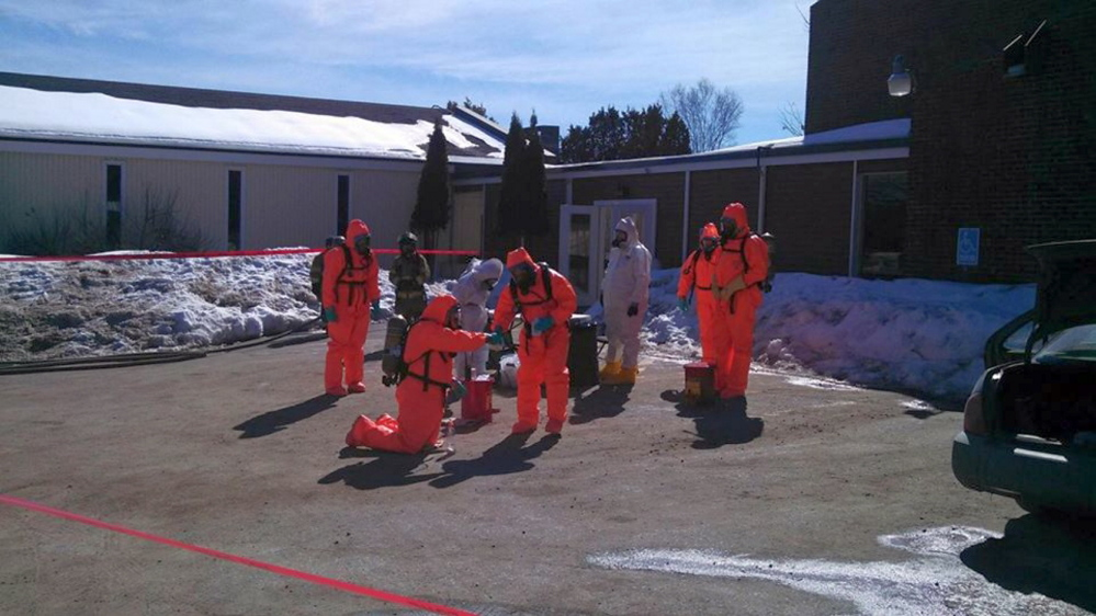 suited up: Drug agents wear protective suits as they search for methamphetamine Friday outside the Waterville Fireside Inn & Suites on Main Street in Waterville.