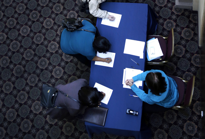 Job seekers sign in before meeting prospective employers at a career fair Jan. 22 at a hotel in Dallas. The Labor Department's figures released Friday were a welcome surprise after recent economic data showed that severe weather had closed factories, lowered auto sales and slowed home purchases.
