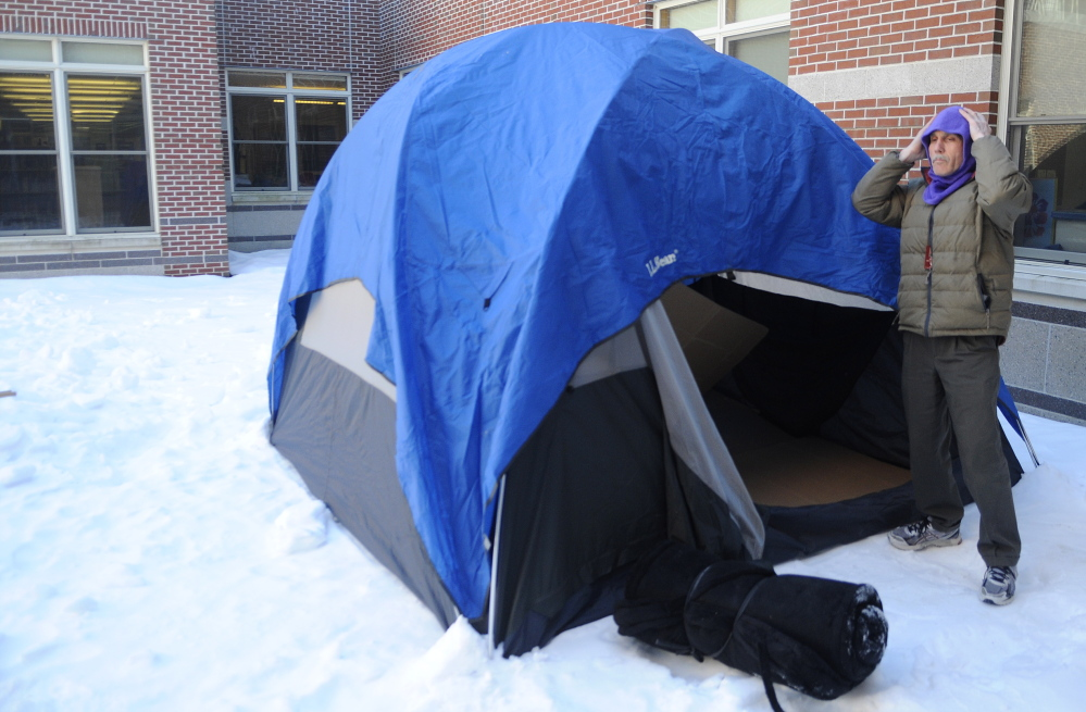OUT IN THE COLD: Cony High School English department chairman Tom Wells covers up his head Thursday while preparing a tent at the school to sleep in over night. Four Cony High School teachers were chosen by students to spend the night outside at the school as part of a fundraiser for the Augusta warming center.