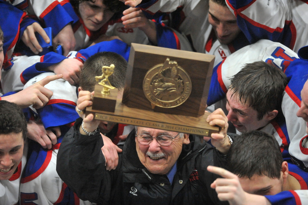 """Staff photo by Michael G. Seamans The Messalonskee High School hockey team celebrates their State Championship with assistant coach Harvey """"Lee"""" Bureau, after defeating Gorham High School 6-1 in the Class B state championship game at the Androscoggin Bank Colisee in Lewiston on Saturday."""