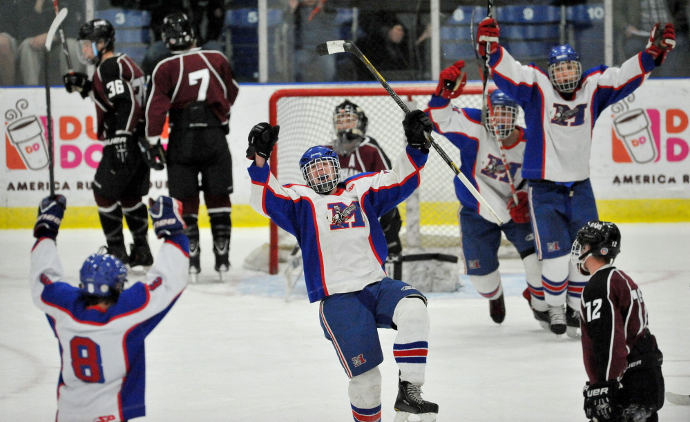 IT'S GOOD: Messalonskee High School's Dan Condon, center, celebrates a goal in the first period of the Class B state championship game Saturday at the Androscoggin Bank Colisee in Lewiston. Messalonskee defeated Gorham 6-1.