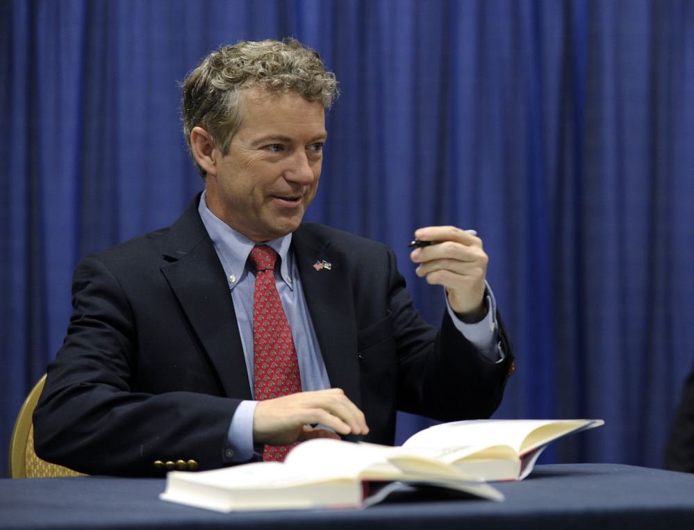 Sen. Rand Paul, R-Ky. signs copies of his book at the Conservative Political Action Committee annual conference in National Harbor, Md., Friday.