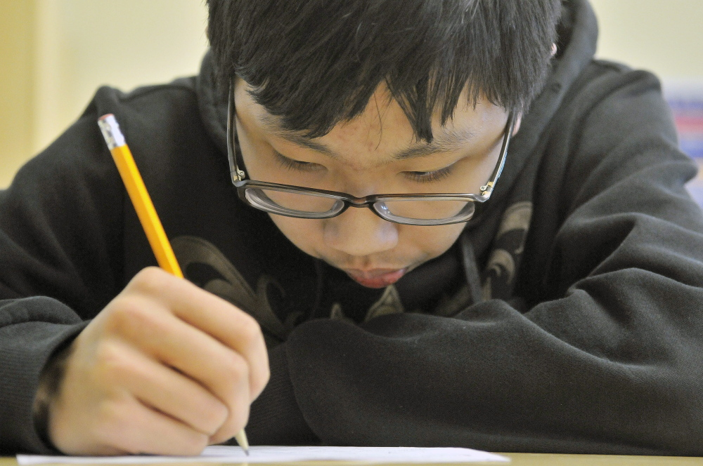 Calculating: Eric Lu, 15, a sophomore at Waterville Senior High School, works through a mathematics problem Wednesday during Waterville Math Team practice at Waterville Senior High School.