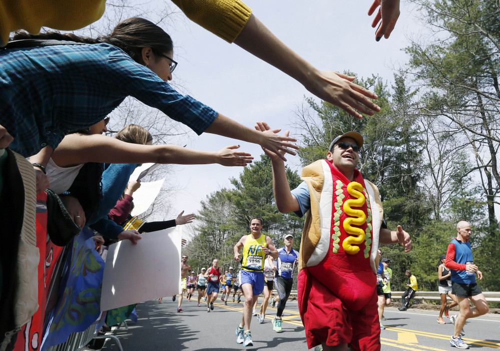 A man dressed as a hot dog runs through Wellesley, Mass., during last year's Boston Marathon. Security will be tightened for the 2014 Boston Marathon after twin explosions killed three people and injured more than 260 near the finish line of the race in 2013. New rules include a limit on the size of water bottles, restrictions on bulky costumes, and nothing covering the face.