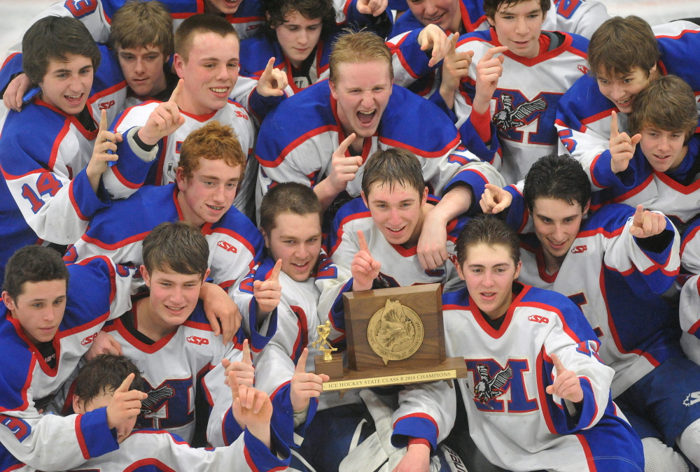 CHAMPIONS: The Messalonskee High School hockey team celebrates their Class B state championship after defeating Gorham High School 6-1 Saturday at the Androscoggin Bank Colisee in .