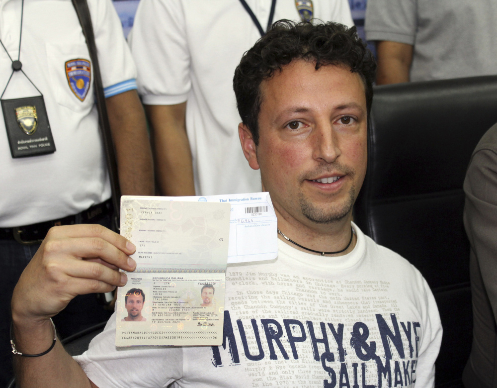 Italian Luigi Maraldi, left, whose stolen passport was used by a passenger boarding a missing Malaysian airliner, shows his passport as he reports himself to Thai police at Phuket police station in Phuket province, southern Thailand on Sunday. Maraldi spoke at a police news conference where he showed his current passport, which replaced the stolen one, and expressed surprise that anyone could use his old one.