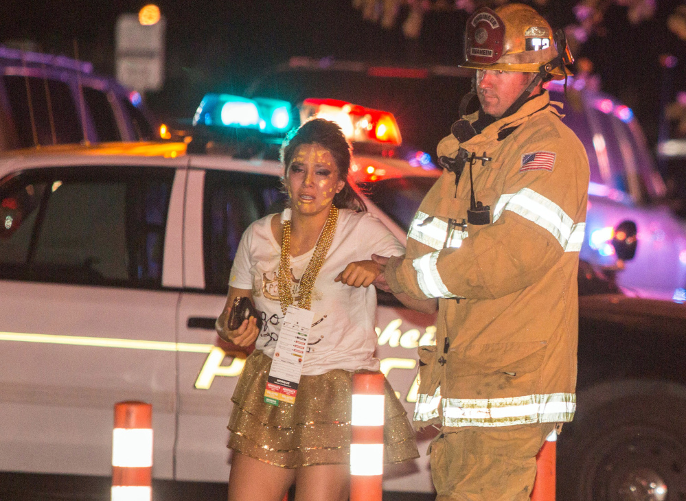 A firefighter assists an injured student after a stage collapsed during a student event at Servite High School in Anaheim, Calif., on Saturday. Authorities said 30-40 people were taken to hospitals with mainly minor injuries.
