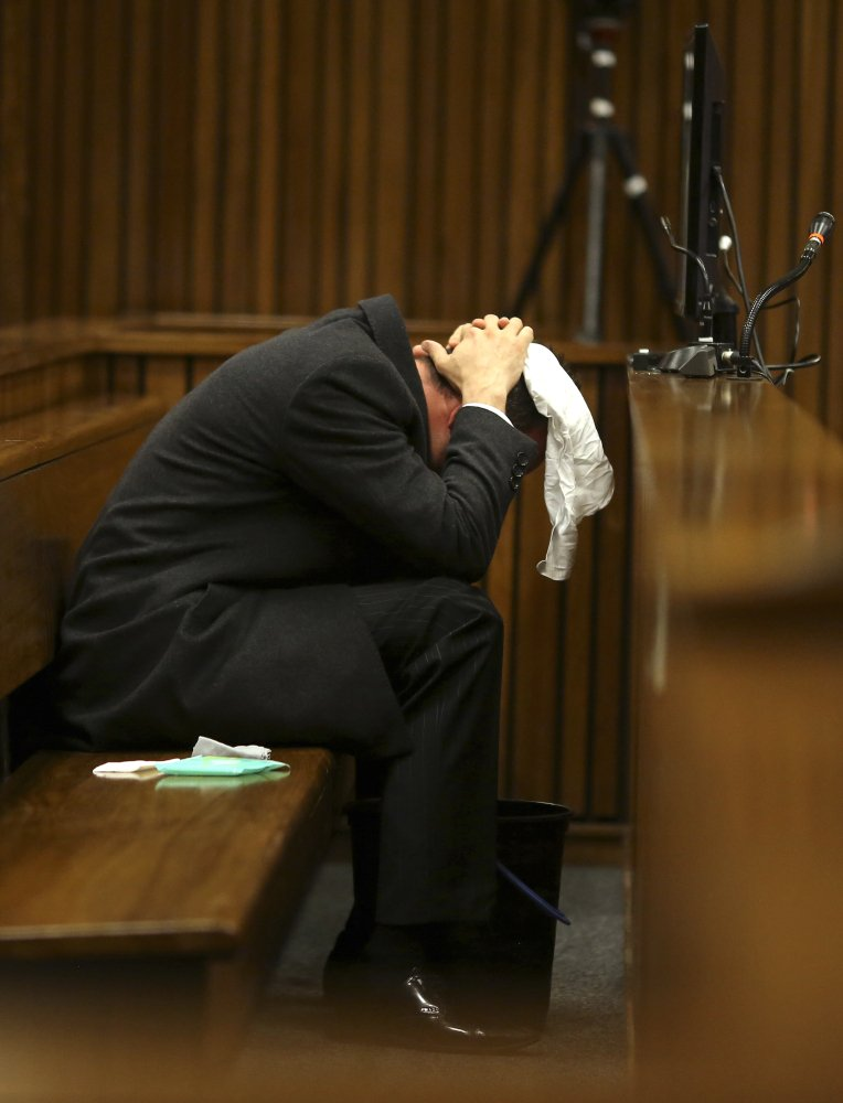 Oscar Pistorius covers his head on Monday after he had reached for a bucket at his feet while listening to cross questioning about the shooting death of his girlfriend, Reeva Steenkamp. Pistorius is charged with the shooting death of Steenkamp on Valentine's Day in 2013.