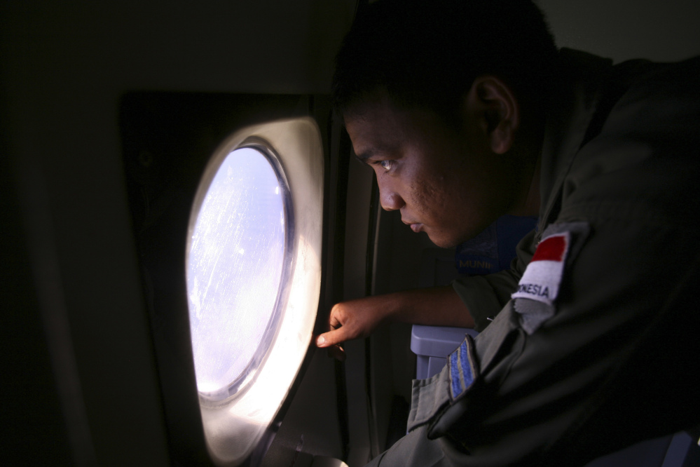 An Indonesian Navy crew member scans the water bordering Indonesia, Malaysia and Thailand during a search operation for the missing Malaysian Airlines Boeing 777 near the Malacca straits on Monday.