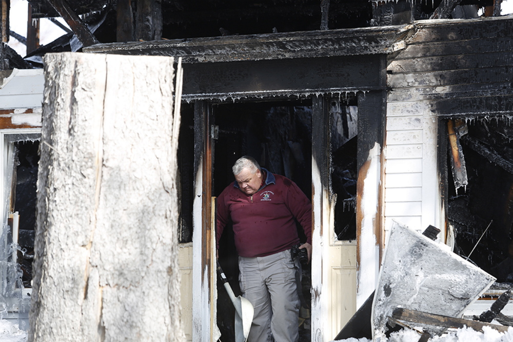 Daniel Young, an investigator with the State Fire Marshal's Office, leaves the house in Limington where a woman was killed in an early-morning fire Monday.