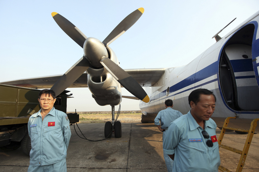 The crew of a Vietnam Air Force aircraft wait at a base Tuesday near Tan Son Nhat airport, Ho Chi Minh City, before a search operation for the missing Malaysian Airlines Boeing 777 over the seas between Malaysia and Vietnam Tuesday.