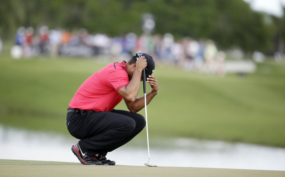PLAYING THROUGH IT: Tiger Woods bows his head on the fourth green during the final round of the Cadillac Championship on Sunday in Doral, Fla. Woods made bogey on the hole. Woods has been suffering from a lower back injury.