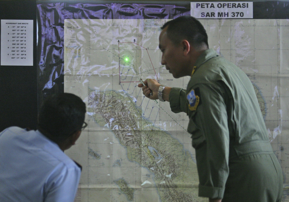 Indonesian Air Force officers examine a map of the Malacca Strait during a briefing following a search operation for the missing Malaysia Airlines Boeing 777 at Suwondo air base in Medan, North Sumatra, Indonesia, on Wednesday. Malaysia asked India to join the expanding search for the missing jetliner near the Andaman Sea, far to the northwest of its last reported position.