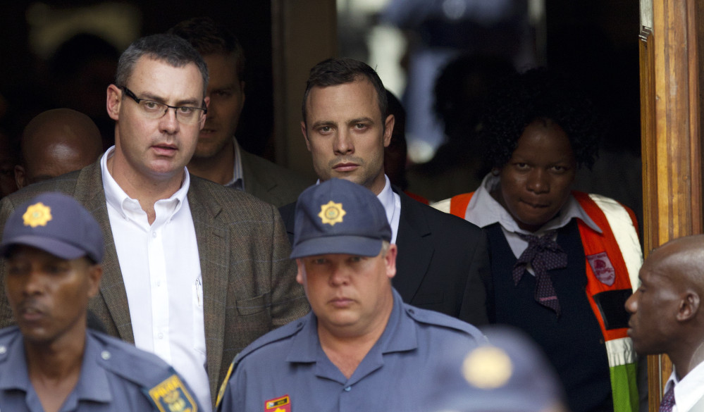 Oscar Pistorius, top center, leaves the high court in Pretoria, South Africa, Wednesday. He is charged with murder for the shooting death of his girlfriend, Reeva Steenkamp, on Valentines Day in 2013.